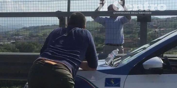 L'uomo appeso alla rete del viadotto sull'A14 mentre parla con un mediatore della questura (foto n.r.)
